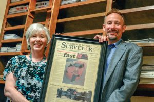 Becky Justice-Hemmann and Robb Justice, owners and founders of the Berthoud Weekly Surveyor, hold teh first edition of the newspaper that was published on June 16, 2004.  John Gardner/ the Surveyor