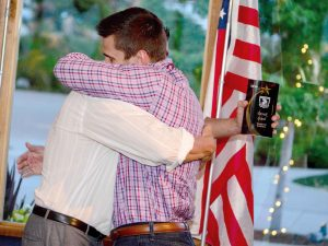 Berthoud High School's track and field coach Colby Schultz hugs 2014 Berthoud Sports Hall of Fame inductee Derek Good as Schultz presented Good with his award. The HOF inducted eight people into the inaugural class at the award and dinner presentation on Thursday, May 29 at Brookside Gardens.  John Gardner/ the Surveyor