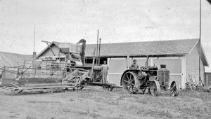 Sid Davis (left) and Ben Green (right) struck a pose on the machinery used to harvest wheat at the High Divide Ranch. While wheat farming was hot, dry work, it did not require time consuming irrigation over the course of the summer.