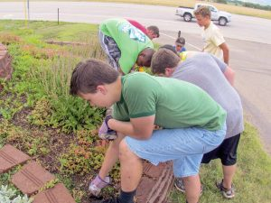 Volunteers from Britton Hill Church of Christ in Oklahoma City work on the flowers at the entrance to Mountain States Children's Home. Bob McDonnell / The Surveyor