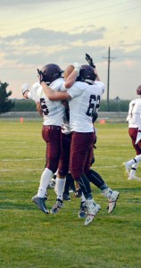 Berthoud running back Jimmy Fate, left, and offensive linemen Stephen Lockard, right, and Brendon Stanley, back, celebrate Fate's touchdown in the first quarter of the Spartans' victory over the Valley Vikings on Friday, Aug. 29 in Gilcrest.  John Gardner / The Survyeor
