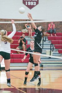 Sophomore Shaylee Pierick blocks a dink from Holy Family as Sarah Howard stands by.