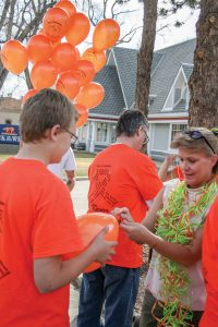 A volunteer holds the a balloon steady as volunteer Laurel Downer ties ribbons on the balloon in preparation to hang them on the light poles along Mountain Avenue in Berthoud in honor of Alex Sabados Day of Kindness last year. Jan Dowker / The Surveyor