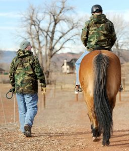 A veteran volunteers to help during the Hearts & Horses for Heroes program event; helping other vets heal with horses.