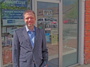 The sign behind Eric Weedin says the insurance agency is open, but this will change in mid-July when the Weedin Agency's Berthoud offi ce will close. The agency will operate in the area but out of the agency's Loveland office. Bob McDonnell / The Surveyor