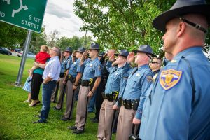 Colorado State Patrol Maj. Tim Keeton commands officers and fellow troopers in attendance to salute a flag dedicated to CSP trooper Taylor Thyfault at a dedication ceremony on July 24 at the corner of Mountain Avenue and Second Street in Berthoud. A second flag was dedicated to trooper Clint Rushing. John Gardner / The Surveyor