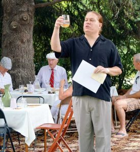 """Michael Georges takes the guests of the Berthoud Historical Society's Garden Party through the wine tasting portion of the event. Here he presents Blue Mountain Vineyard's Pinot Grigio and demonstrates placing a frozen peach slice into their glass, explaining how the flavors of the peach incorporate with the wine as it thaws. The """"Garden"""" was filled with sophistication in the music, fruit and cheese platters, and the dress of the guests.  May Soricelli / The Surveyor"""
