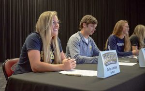 Taylor Armitage, left, smiles at family prior to the Letter-of-Intent signing ceremony at Berthoud High School on Nov. 11, along with Isaac Bracken, middle, and Kristina Cavey, right. John Gardner / The Surveyor