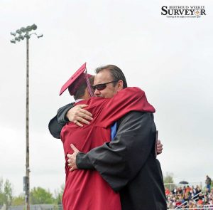 Cliff Montano hugs 2015 Berthoud High graduate Tyler Pechin at the commencement ceremony in May. Surveyor file photo