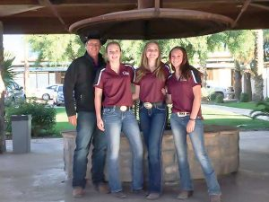 Berthoud Equestrian Club members Haley Fischer, right, Elana TerAvest, middle, and Mikayla Davis pose for a photo along with coach Mark Guynn at a recent competition in Arizona.