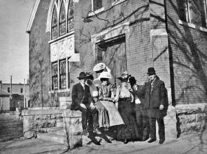 The Berthoud High School Class of 1907 was comprised to eight students. The male graduates, Fred Hartford (left) and Clifton McGlothlan (right) flanked their female counterparts when they posed for a photo on the steps of the United Brethren church. Emma Bennett (center) was the only young woman who faced the camera. Professor Van Hoose stood in the shadows between Bennett and McGlothlan. Photo courtesy of Ludlow Collection/ Berthoud Historical Society