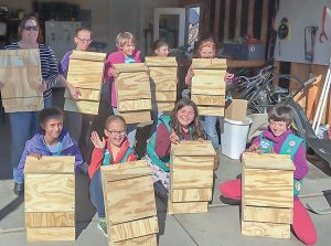 Girl Scout Troop 70700 pose for a photo with the bat houses they built for a group project. Top row from left: Jen Rotar (leader), Alexis Wilcox, Sara Rotar, Lucy Hein, Zaida Riggert-Foster. Bottom row: Konjit Mewes, Ronnie Moss, Audriana Gutierrez, Kenyan Clarkson. Photo courtesy of Jen Rotar / The Surveyor