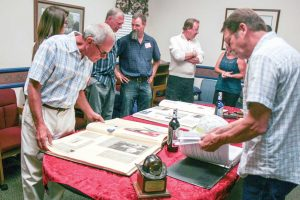 Former volunteer firefighters reminisce over old books and photographs at the volunteer firefighter dinner on June 6 in Berthoud. Becky Justice-Hemmann / The Surveyor