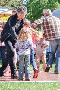 Berthoud Area Chamber of Commerce Director Deanne Mulvihill dances with a young girl at a previous Oktoberfest in Berthoud. Mulvihill is in her fourth year as chamber director and memberships are stronger than ever. Surveyor file photo