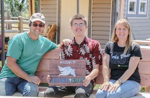 Guy and Kaarin Scoma, founders of Guided Hope, enjoy a moment of relaxation with Eagle Scout Aaron Carlson on one of the new benches he built for the ranch. The benches were part of Carlson's Eagle Scout project. Photo courtesy of Guided Hope