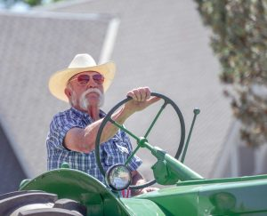 Berthoud resident and agriculture aficionado Bill Markham is photographed driving a tractor during the 2016 Berthoud Day Parade in June. Markham is a prominent local figure in the agriculture community and is also a champion to the 4H kids that raise livestock for auction. John Gardner / The Surveyor