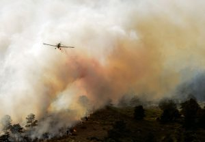 A single engine air tanker drops slurry near a house west of County Road 27E during the Hertha Ridge Fire on Aug. 17. John Gardner / The Surveyor