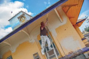 Mark Shafer, of Faith Painting, sprays a fresh coat of paint on the exterior of the Berthoud Train Depot in Berthoud on July 29. The historic Berthoud Train Depot is the meeting place of the local chapter of the Lions Club. The Lions Club has been renovating the interior of the building for several months and was able to get the exterior painted through donations. According to Ken Schwols, Lions Club area leader, the club is also interested in having some murals painted at the depot. Any interested artists can contact Schwols at: kschwols@ yahoo.com. John Gardner / The Surveyor