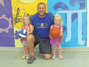 Turner Middle School athletic director and dean of students, Steve Frye, with the help of daughters, Victoria and Violet, get ready for the new school year. Bob McDonnell / The Surveyor