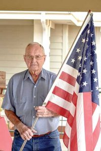 Stan Edmisten holds an American flag while posing for a photo at his Berthoud home. Edmisten recently particiapted in an Honor Flight trip to Washington D.C. to visit the World War II memorial.   Bob McDonnell / The Surveyor