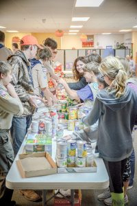 Members of local Boy Scouts and Girl Scouts troops prepare and seperate food items before making the Thanksgiving baskets Monday night. The group together made over 40 baskets that will provide a complete Thanksgiving meal to local families. John Gardner / The Surveyor