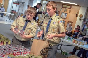 Boy Scouts Ty Rotar, right, and Martin Juhasz discuss what type of soup to place in one of the Thanksgiving baskets that the Boy Scouts and Girl Scouts prepared for local residents at the Berthoud United Methodist Church Monday night. John Gardner / The Surveyor