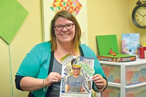 """Reading therapist Valerie Backo smiles as she displays a picture one of her students made to convey he went from hating reading to an """"I am a reader,"""" mindset. Bob McDonnell / the Surveyor"""